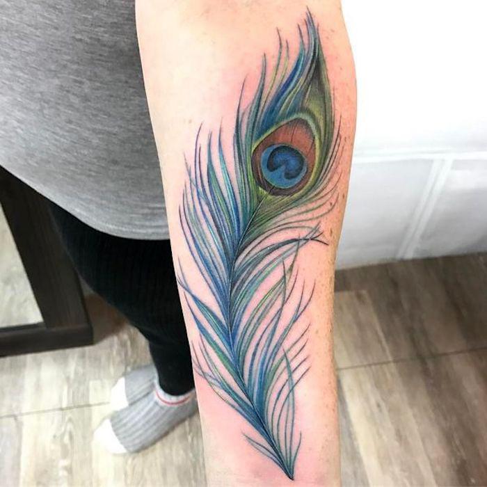 großes pfauenfeder tattoo am unterarm, tattoos für frauen