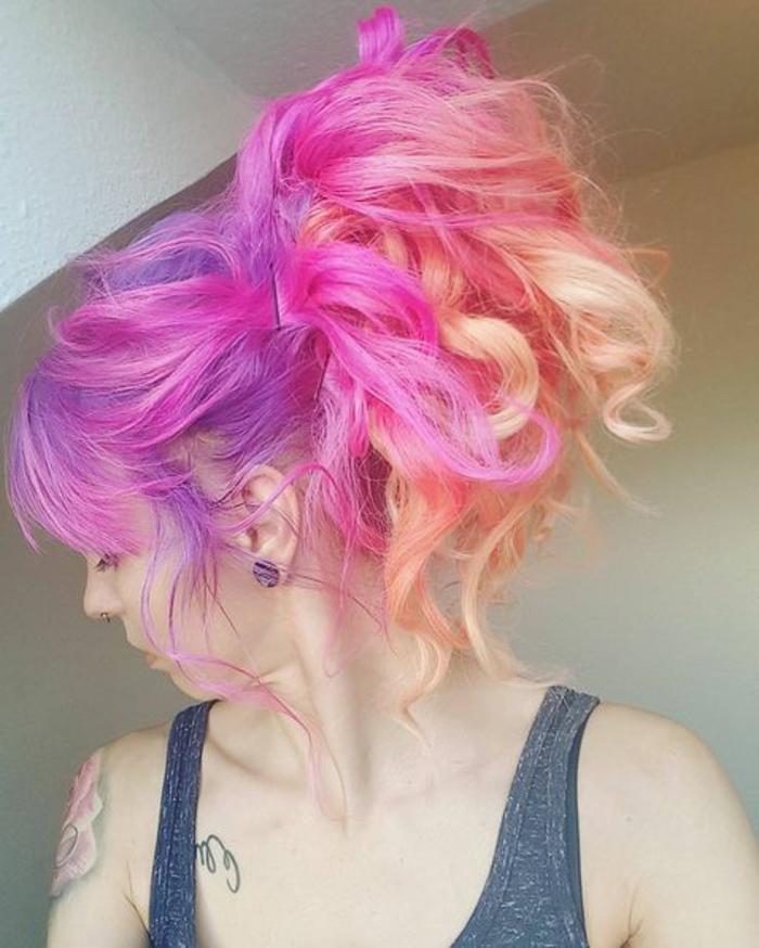 lockiges Haar mit Seitenpony, Haare mit Haarklammern hoch stecken, lila Ansatz mit pinken Strähnen und pfirsichrosa Längen, Schultertattoomiit Blumenmotiv