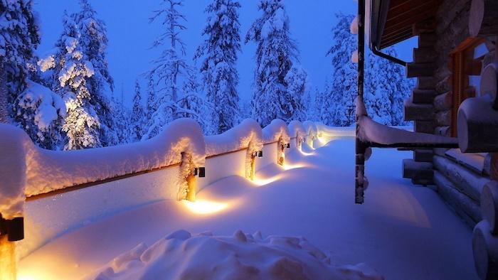 ein haus und eine terrasse mit schnee - ein wald mit vielen großen bäumen un der nacht - schöne winterbilder