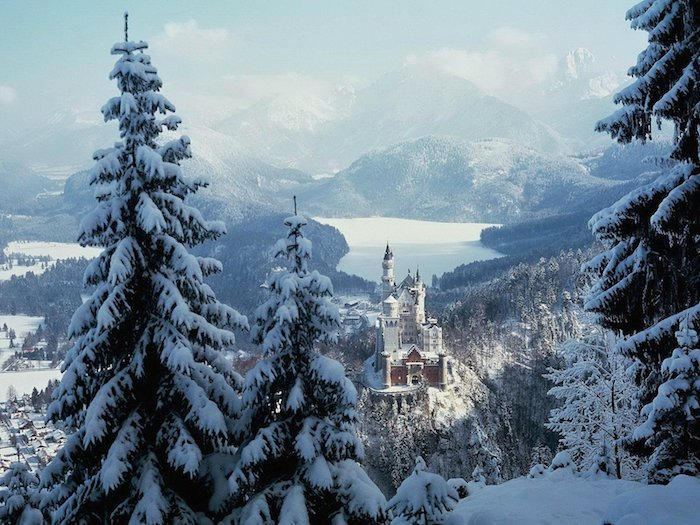 ein romantisches winterbild mit einem weißen schloss mit türmen und einem wald mit vielen bäumen - berge mit schnee - blauer himmel mit weißen wolken