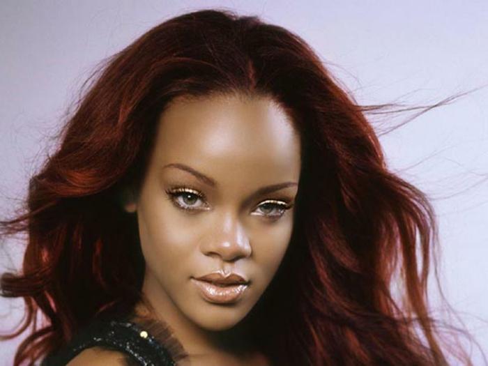 Rihanna mit rötlichen freifallenden Haaren und großem Stirn, Schokoladenhaut und grünen Augen mit goldenen Lidschatten, Afroamerikanerin mit großer Nase und dicken Lippen, Rihanna mit extravagantem schwarzen Tüllkleid