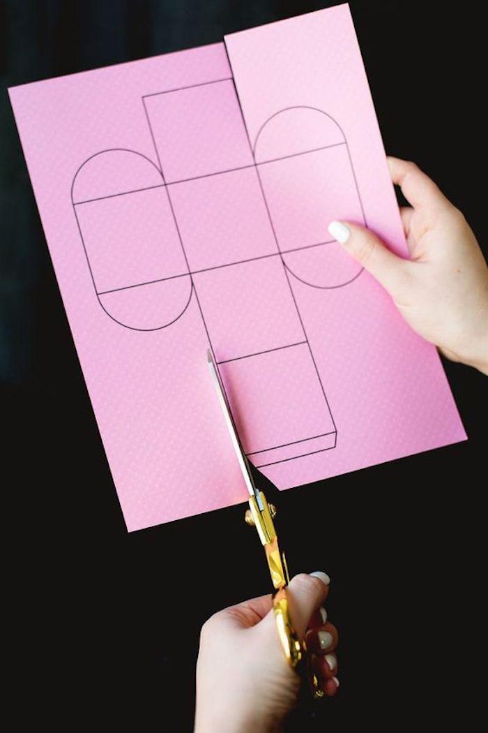 eine Schachtel Vorlage auf rosa Papier mit der Schere schneiden - Pappschachtel
