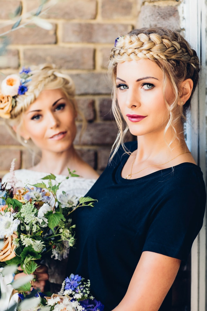 Zopfkranz mit Blumen verziert, zwei blonde Frauen, olivfarbener Teint und leichtes Tages-Make up