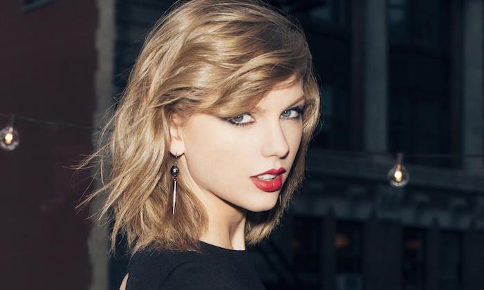 dunkelblonde Haare Taylor Swift mit einem roten Lippenstift und längliche Ohrringe