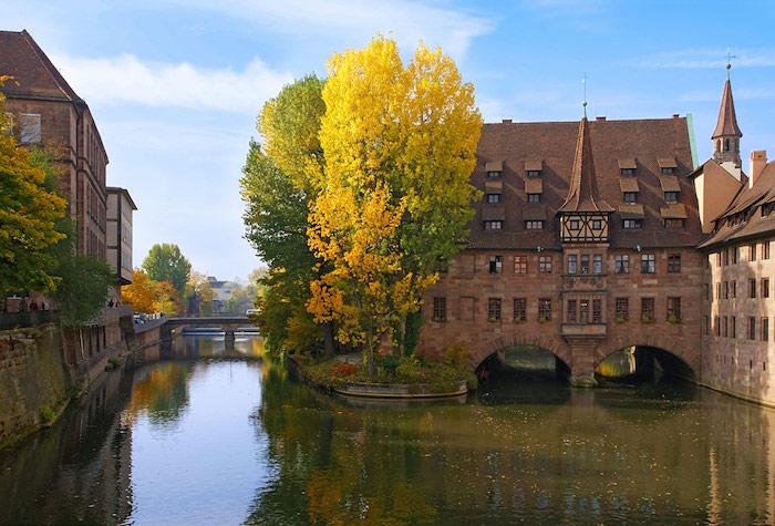 die schönsten urlaubsziele in bayern, deutschland fluss und gebäude in dem fluss oder darüber brücke herbst bäume in gelb orange und grün