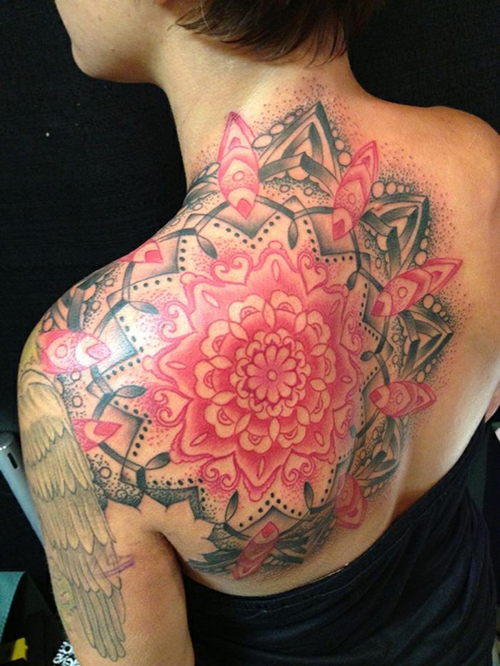 riesiger Ornamental-Tattoo an der linken Schulter und am linken Schulterblatt, oben bis zum Hals und unten bis zum Rücken, schwarz-roter Tattoo mit vielen schwarzen Punkten und roten Herzen, kleine Herzenmotive, Frau mit kurzem Haarschnitt und schwarzem Top
