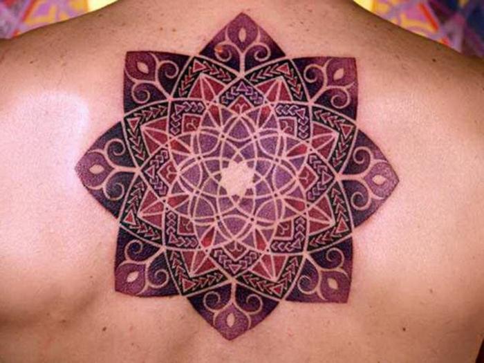 Rückentattoo im Zentrum des Rückens in Weinrot, Lila und Violett, Mandala ohne Konturen mit vielen Triangeln, Rücken mit vielen Muttermalen