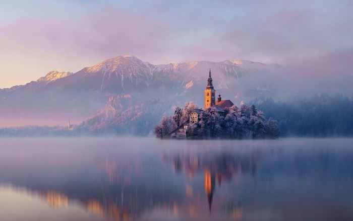 romantisches winterbild - ein see mit einer insel mit einer kirche und kleinen häusern und bäumen - berge mit schnee und pinken wolken