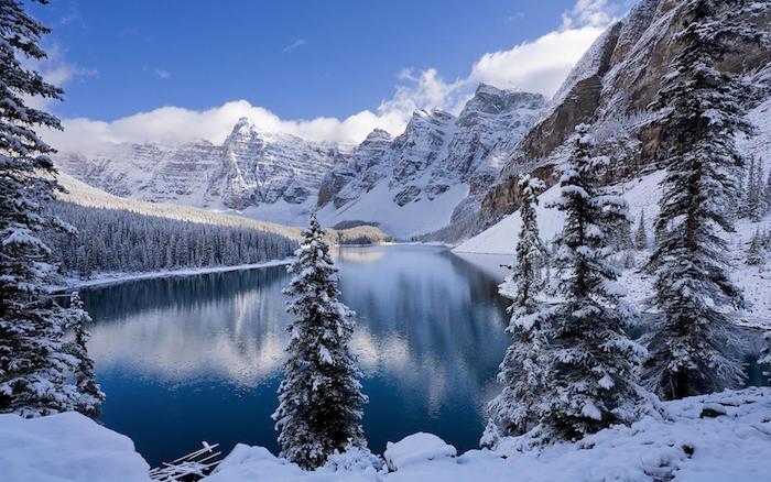 romantisches winterbild - himmel mit weißen wolken - weiße berge mit steinen - ein wald mit bäumen