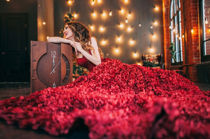 Rotes Ballkleid, Silvester Outfit, trägerloses Kleid, Wanduhr aus Holz, zwölf Uhr, Lichterketten an der Wand
