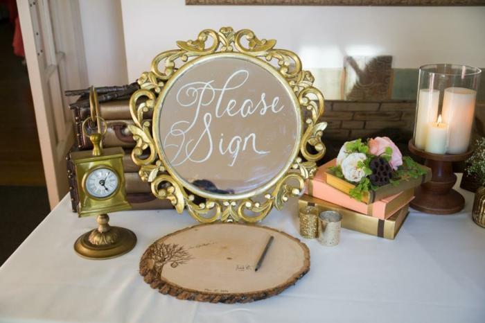 Hochzeit in Landhausstil, Spiegel mit goldenem Rahmen, Holzstück zum Aufschreiben, weiße Kerzen und Bücher