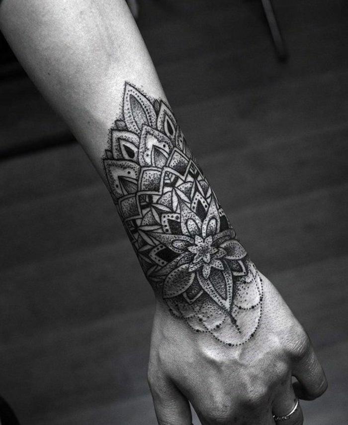 Mann mit dünnem Arm ohne Haare mit einem Handgelenk-Tattoo mit Mandala, Armtattoo mit Kettenmotiv