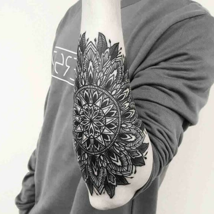 Mann mit kompliziertem Unterarmtattoo mit einem großen Mandala in schwarzer Farbe mit vielen Blättern und Kreisen, graue Bluse mit langen Ärmeln mit weißem Buchstaben-Print