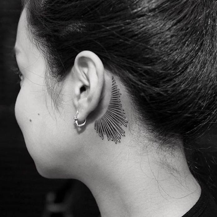 eine junge frau mit einem schwarzen tattoo hinterm ohr und einem kleinen ohrring