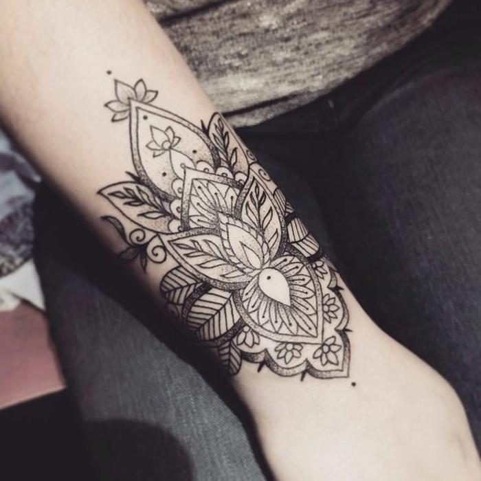 Handgelenk-Tattoo mit zwei kleinen grauen Lotusblumen, Spiralen und vielen Blättern, Verzierung mit kleinen Punkten, schwarze Jeans und graue Bluse