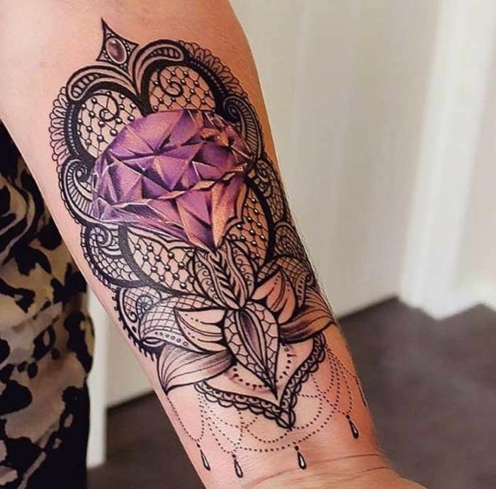 große Tätowierung mit länglicher Form mit Kreisen, Tropfen und Spiralen in schwarzer Farbe und einem großen lila Diamant