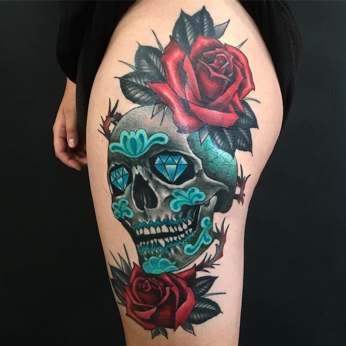 ei n totenkopf mit rosen tattoo - totenkopf mit zwei blauen diamanten und zwei großen roten rosen mit grünen blättern