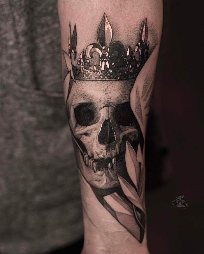 eine hand mit einem großen tattoo mit einem weißen totenkopf mit schwarzen augen und einer krone