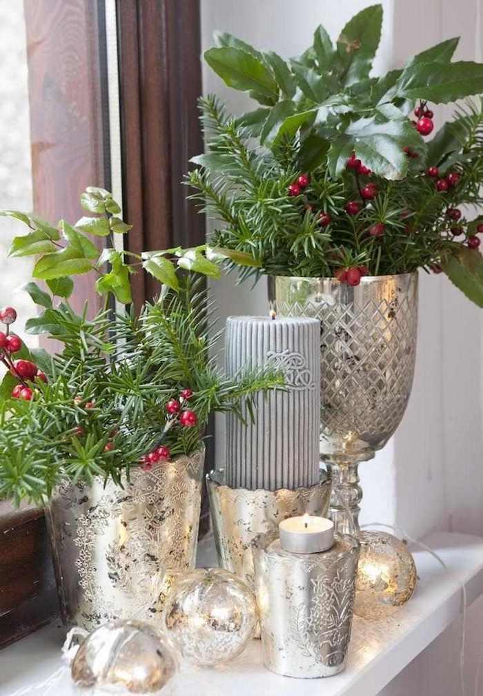 fensterdeko weihnachten basteln glänzende deko ideen silberne vasen kerzen grüne zweige rote früchte