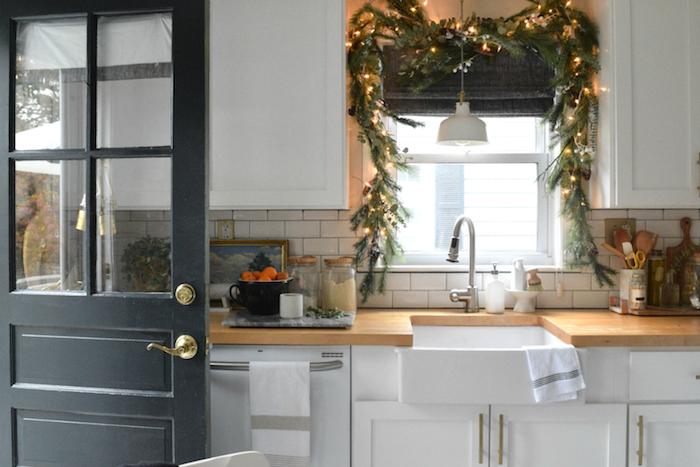 weihnachtsbeleuchtung fenster in der küche mit grünen zweigen und kleine lichter lichtkette dekorieren