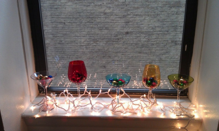 drei Cocktailgläser aus farbigem Glas, gefüllt mit kleinen Christbaumkugeln in verschiedenen Farben, zwei Weingläser aus rotem und gelbem Glas, Lichterkette mit stark brennenden Lichtern, Fenster mit dunklem Rahmen und Aussicht zum Nachbarhaus