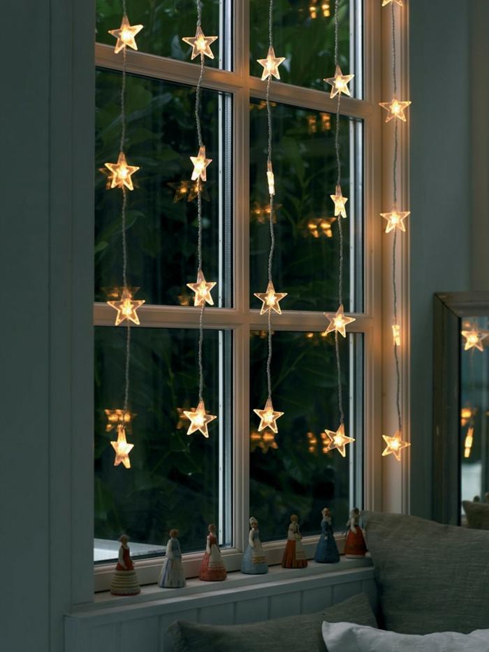 fünf Lichterketten aus LED-Sternen, kleine Frauenfiguren aus Keramik, Haus mit hellblauen Wänden, groér Spiegel mit grauem Rahmen in der rechten Ecke hinter der hellgrauen Couch, hellgraue und weiße Couchkissen, Holzverkleidung für Wand