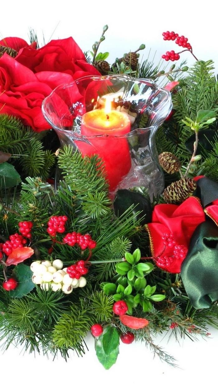 eine Kerze in der Mitte von roten Blumen und grüne Zweige - Weihnachtgesteck