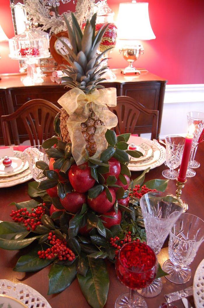 Weihnachtsgesteck aus Früchten - Äpfel und Ananas von grünen Zweigen umgeben
