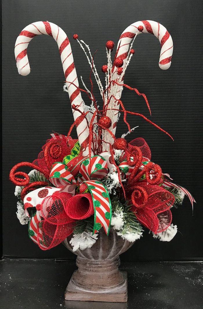 Weihnachtsgesteck aus roten Blumen, Schleifen und Süßigkeiten in einer alten Vase