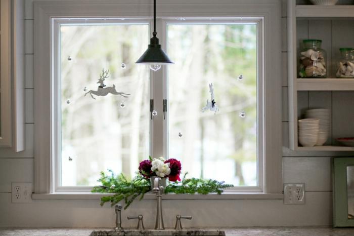 weiße Küche mit Nadelbaumzweigen und einen Strauß von roten und weißen Rosen am Fenster, Tisch mit Marmorpatte, Waschbecken mit zwei Wasserhähnen, Wasserhahn für warmes Wasser, Wasserhahn für kaltes Wasser, Küche mit weißen Fliesen an der Küchenrückwand, offenes Wandregal für Geschirr, Tellerregal mit weißen Kaffeetassen und zwei Einmachgläsern