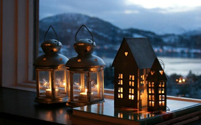 Deko für Heiligen bend - Häuser aus Karton Teelichter drinnen, Löcher in der Form von Herzen, zwei Laterne aus Glas und Metall, ein Haufen große Bücher, Fenster mit Aussicht zum Gebirge, Schnee im Gebirge