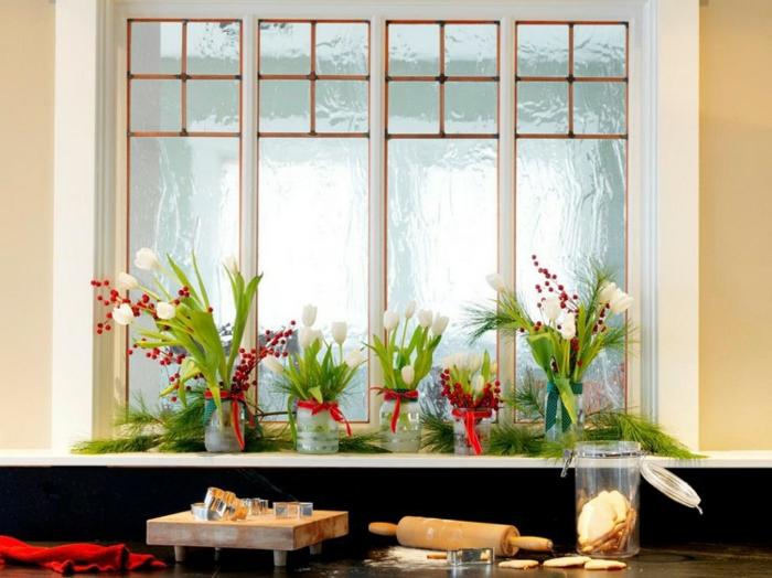 Küchenfenster mit weißen Tulpen mit langen hellgrünen Blättern, gestellt in Einmachgläsern, verziert mit roten Schleifen und kleinen Mistelzweigen mit roten Früchten, Holztbrett mit vielen Ausstechfoormen darauf, roter Handtuch aus Baumwolle, frisch gebackene Ingweirkekse, Teig mit Nudelholz ausrollen, Küchentisch bestreut mit Mehl, gut bemehlte Arbeitsfläche