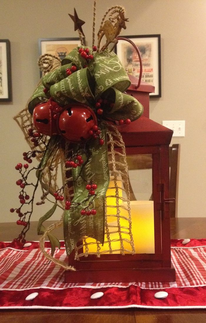 Weihnachtsgesteck aus einer Laterne mit zwei Glocken und eine grüne Schleife