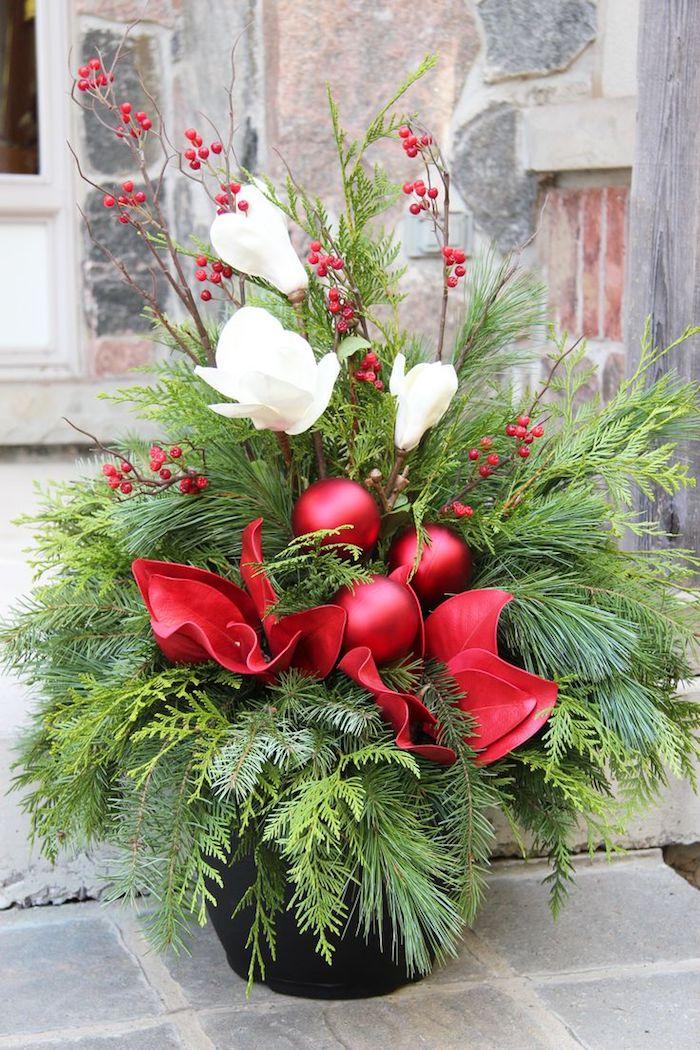Adventsgestecke aus Naturmaterialien - kleine Zweige aus dem Weihnachtsbaum und weiße Blumen