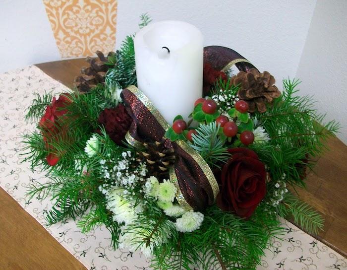 Adventsgestecke aus Naturmaterialien - grüne Zweige und rote Schleife, weiße Kerze