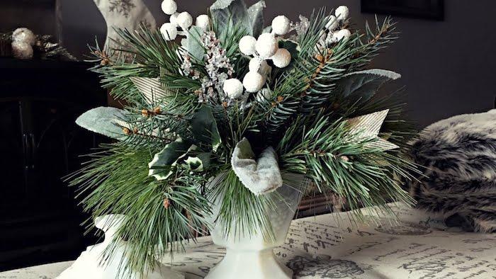 eine weiße Vase mit grünen Tannenzweigen und weiße Blumen - Gestecke selber machen