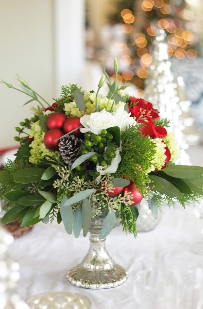 eine silberne Vase mit roten Kugeln und Zapfen, weiße Blumen - Gestecke selber machen