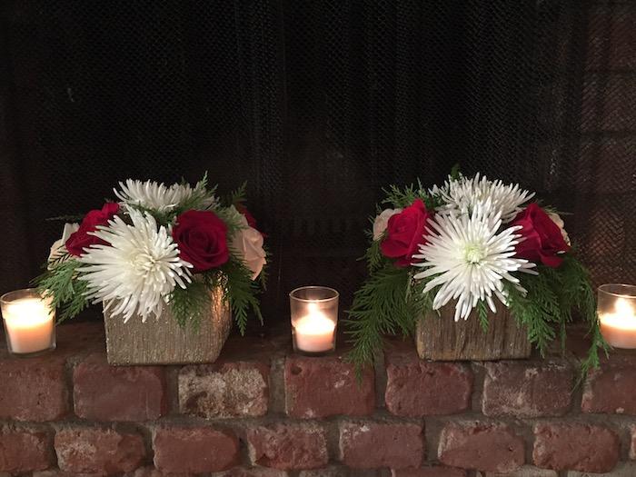 Adventsgestecke aus Naturmaterialien - drei Kerzen auf einer Steinwand mit Kerzen dazwischen