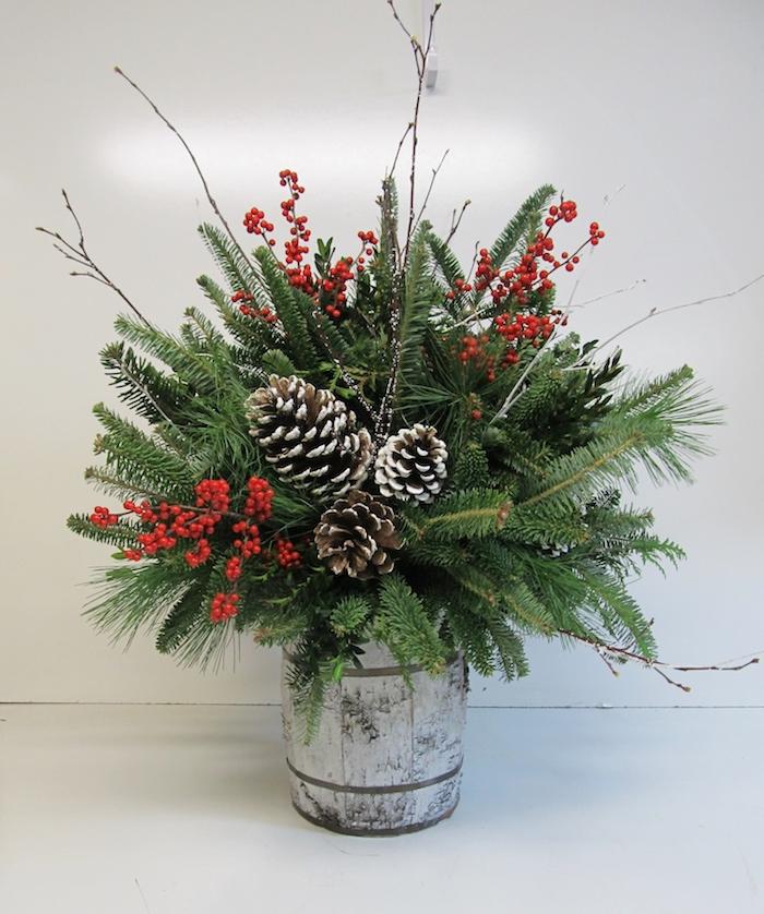 in einer silbernen Vase sind drei große Zapfen, Hagebutten und Tannenzweige Gesteck Weihnachten