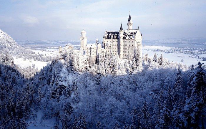 winterbild mit einem großen weißen schloss mit türmen und einem wald mit vielen bäumen mit schnee - ein himmel mit weißen wolken