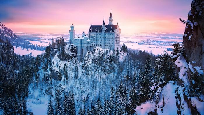 ein großes weißes schloss im sonnenuntergang - wald mit schnee und bäumen - himmel mit pinken wolken