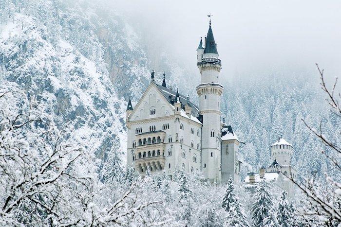 ein großes weißes schloss mit großesn türmen - ein winterwald mit bäumen und schnee