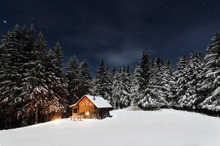 ein kleines haus aus holz und ein wald mit vielen bäumen und schnee - ein himmel mit weißen sternen und wolken