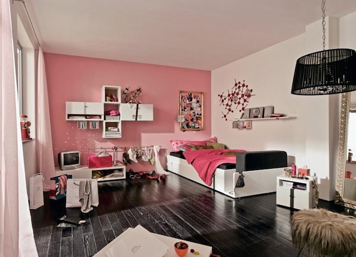 jugendzimmer möbel ideen schwarzer boden aus holz rosarote wände mit deko in weiß regale mit bücher und deko kleines fernseher bett lampe