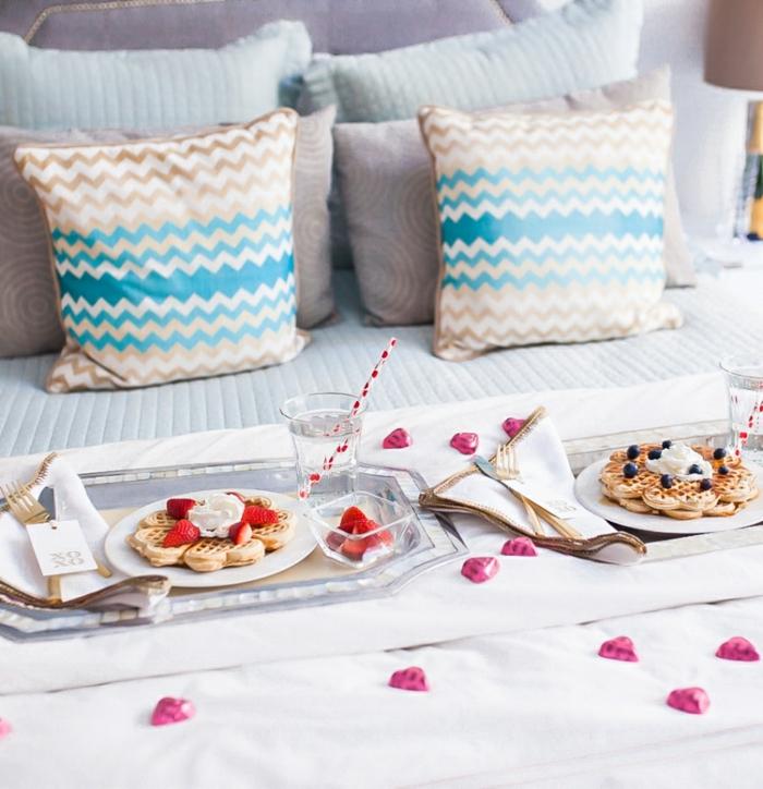 Frühstück im Bett zum Valentinstag, belgische Waffeln mit Sahne und Beeren, Schokoladen Herzen überall