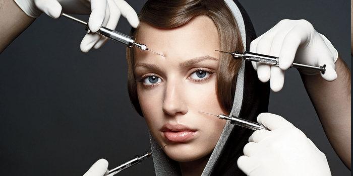 zwei Ärzte spritzen Botox ins Gesicht einer jungen Frau
