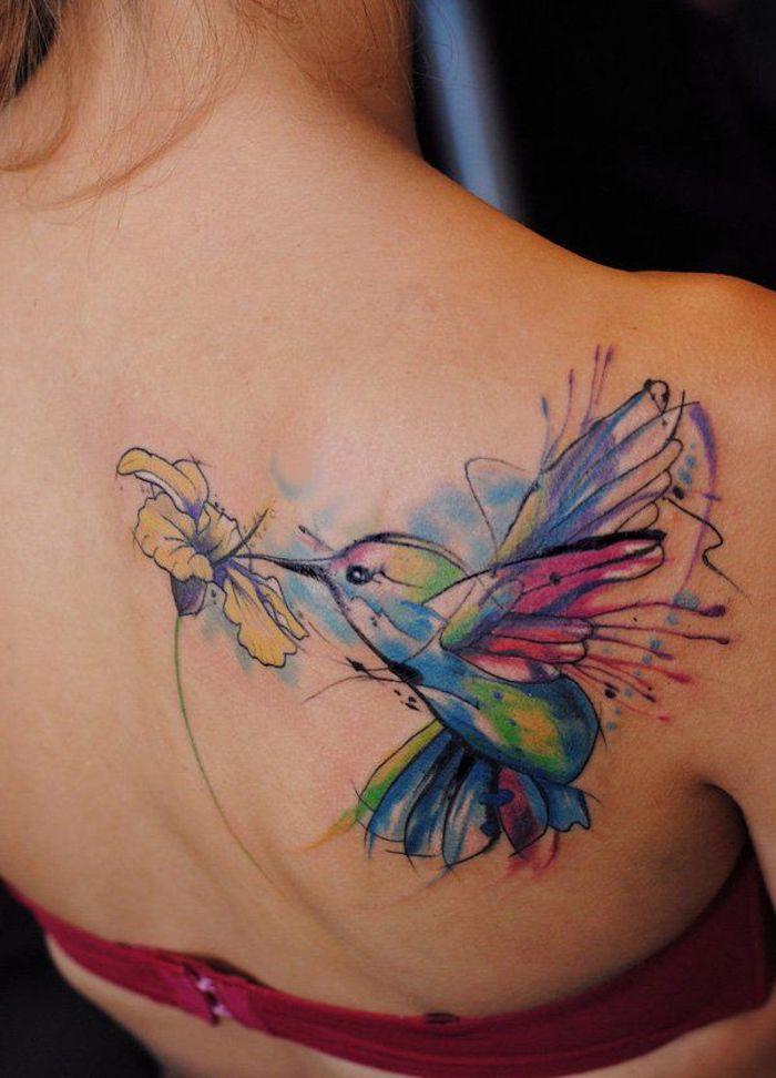 frau mit farbigem kolibri tattoo am rücken, vogel mit blume