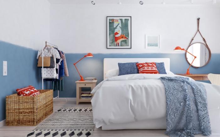 Wand in zwei Farben, ein Wandbild und ein Plakatt in schwarzem Rahmen, Plakatt mit Fuchs, kleiner Nachttisch mit einer orangen Leselampe, runder Wandspiegel mit braunem Rahmen, schmale Fußmatte mit Print, Flechtkorbzur Aufbewahrung von Schlafdecken und Kissen, zwei blaue Kissen mit gestrickten Bezügen, roter Kissen mit winterlichem Motiv, hellblaue Strickdecke