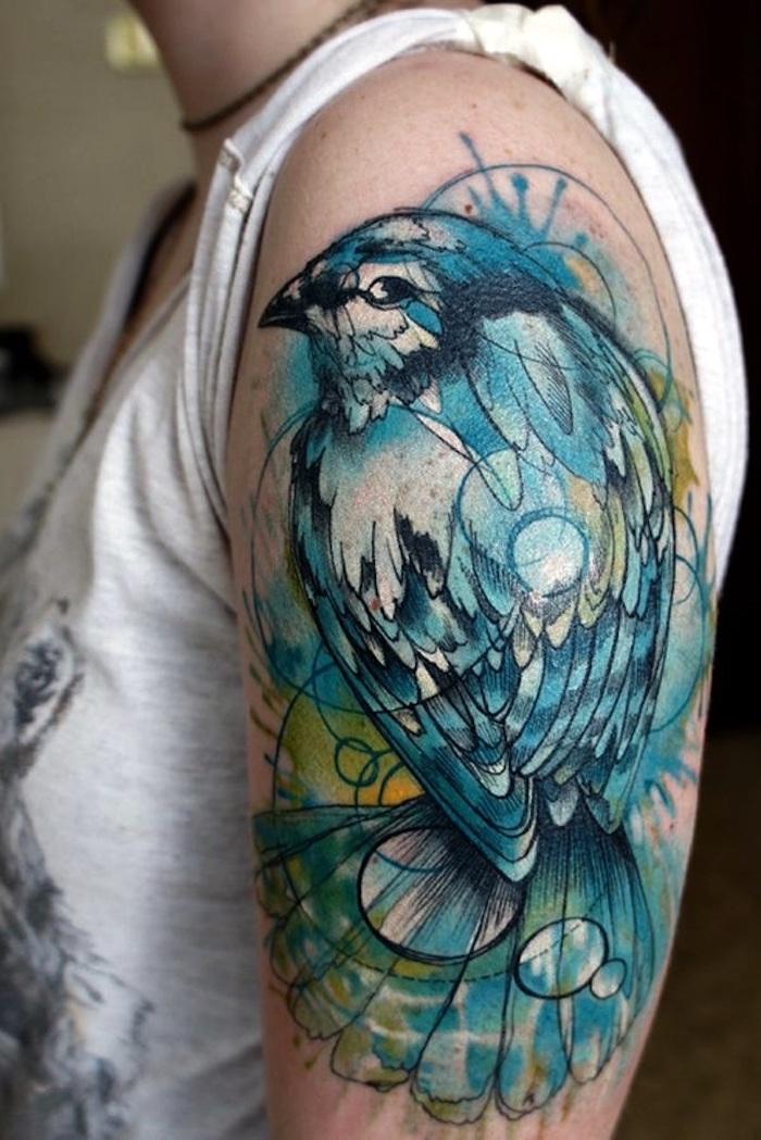 großes farbiges vogel tattoo am oberarm, blaues vogel, wasserfarben