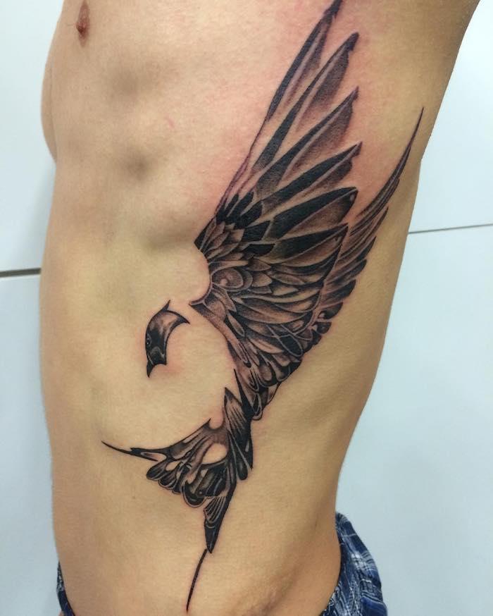 mann mit schwarz-grauem vogel tattoo an der körperseite